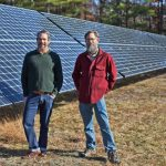 Aaron Anker (left) and Nat Peirce, owners of Grandyoats, stand in front of solar panels powering their granola company in Hiram, Maine.